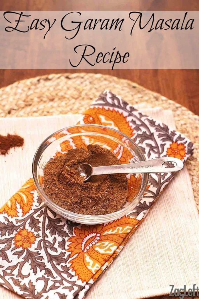 Garam masala spice in a small glass bowl with silver teaspoon
