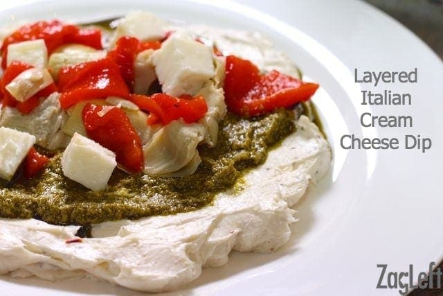 Layered Italian Cream Cheese Dip topped with pesto, artichoke hearts, roasted red peppers, and mozzarella cheese on a plate