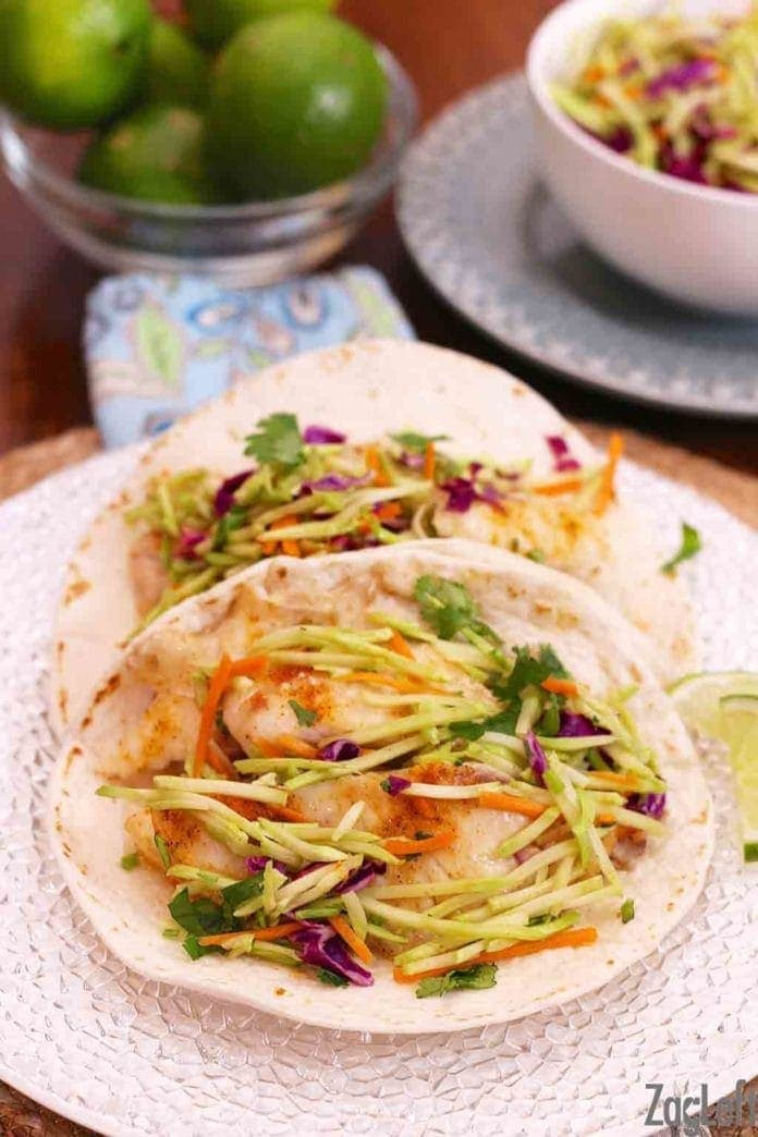 two fish tacos topped with a broccoli slaw on a plate surrounded by fresh limes   one dish kitchen