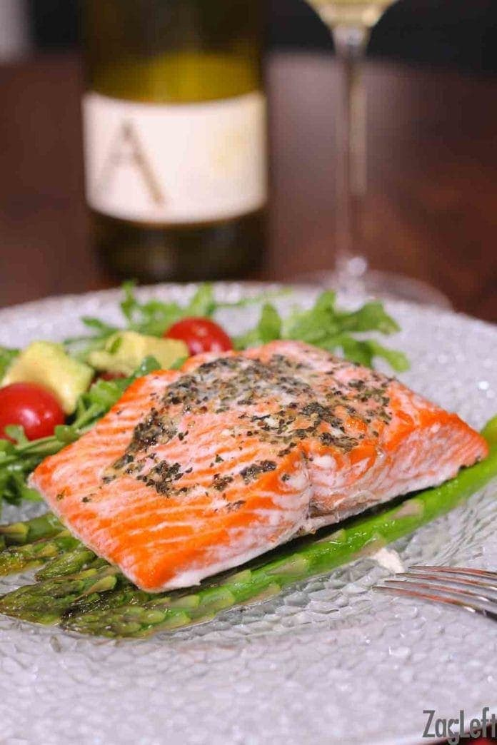 Baked Salmon on a bed of asparagus and a side salad of arugula, cherry tomatoes, and avocado slices plated on a wooden table with a glass of white wine in the background
