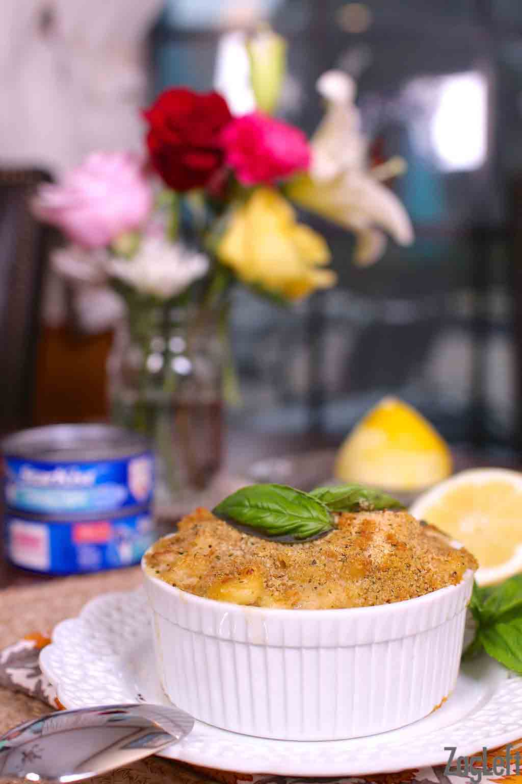 Tuna casserole in a small bowl on a wooden table with two cans of tuna and a vase of flowers in the background