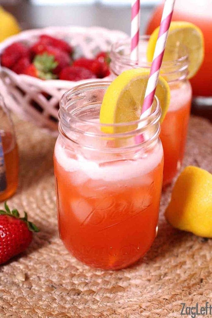 Two glasses of strawberry lemonade in mason jar glasses with a paper straw and lemon wheel garnish with a bowl of strawberries in the background
