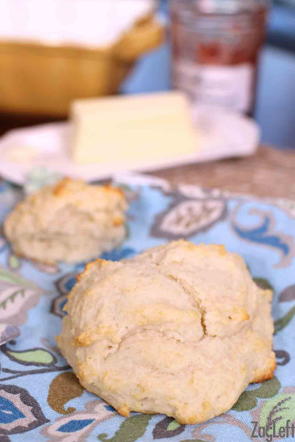 A closeup of a biscuit with another biscuit and a stick of butter in the background all on a blue cloth napkin