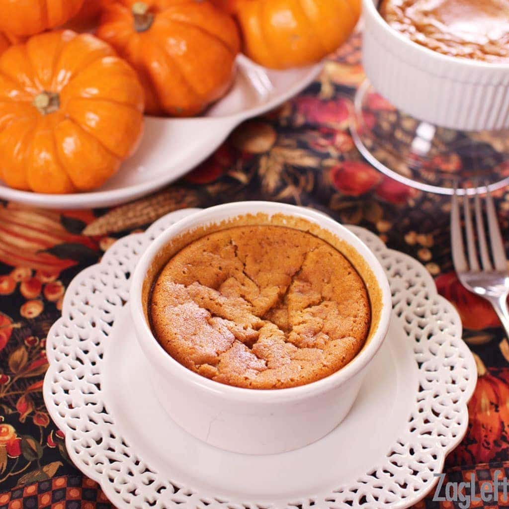 A mini pumpkin pie in a small circular baking dish on a fall themed tablecloth with small pumpkins in the background