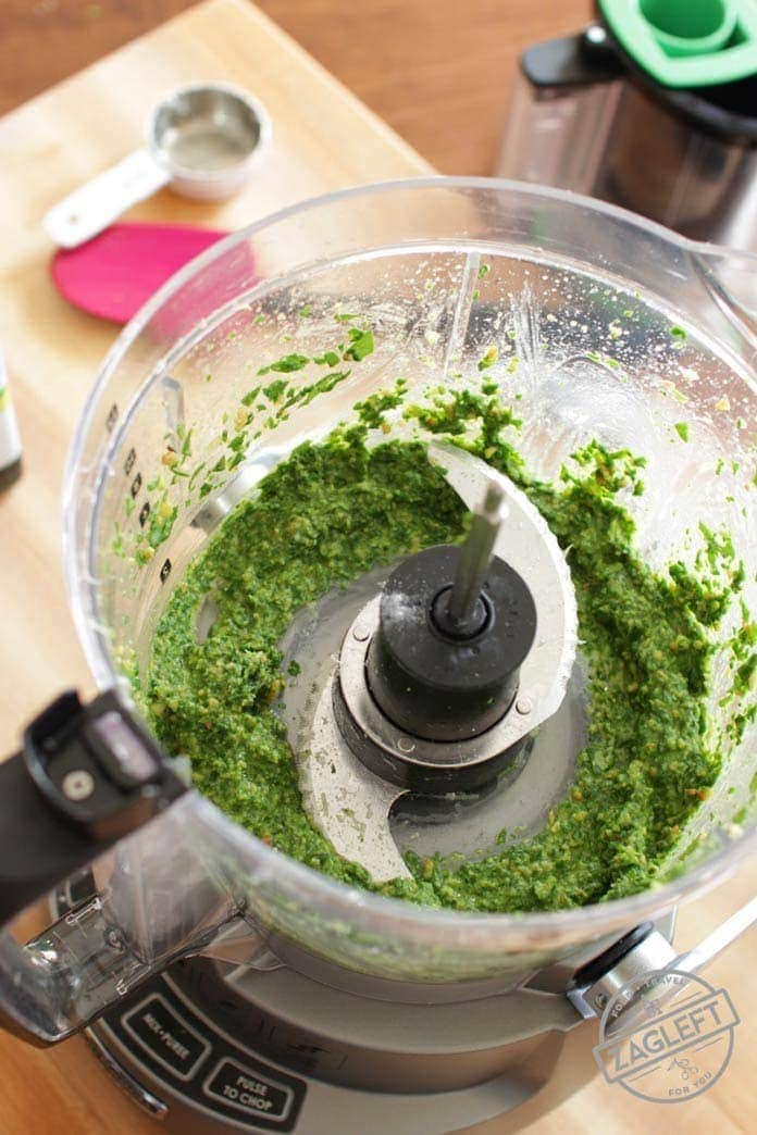 Ingredients for pesto all chopped and smoothed together in a food processor
