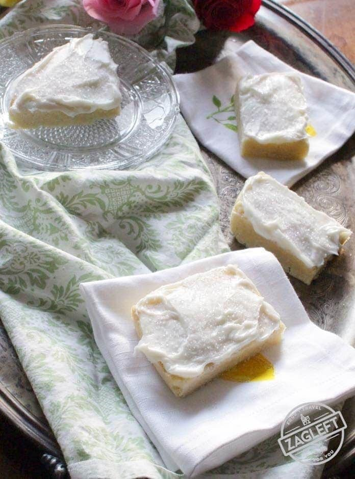 Four frosted sugar cooke bars spread out on a metal tray- one cookie on a small glass plate and the other three on white cloth napkins
