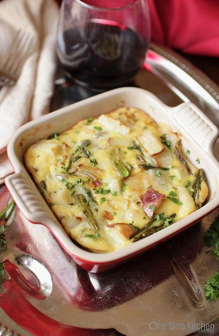 Potato and asparagus crustless quiche in a small baking dish on a metal tray with a glass of red wine