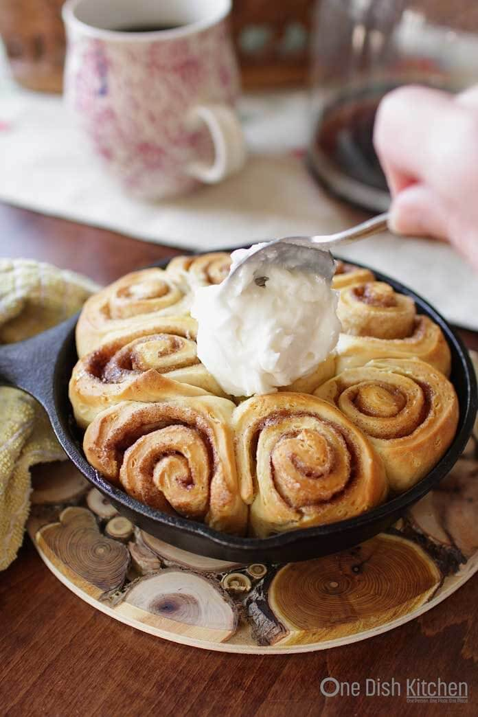 Spreading frosting over the cinnamon rolls | One Dish Kitchen