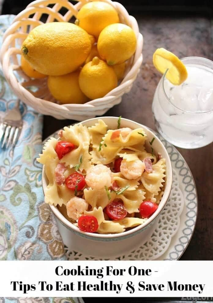 An overhead view of a bowl of bowtie pasta with cherry tomato halves and shrimp next to a bowl of whole lemons and a glass of ice water with a lemon wheel garnish