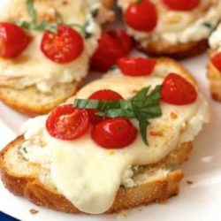 Caprese toast with green pesto and tomatoes on top