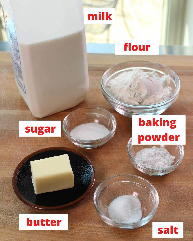 flour, baking powder, sugar, butter, salt and milk on a table.