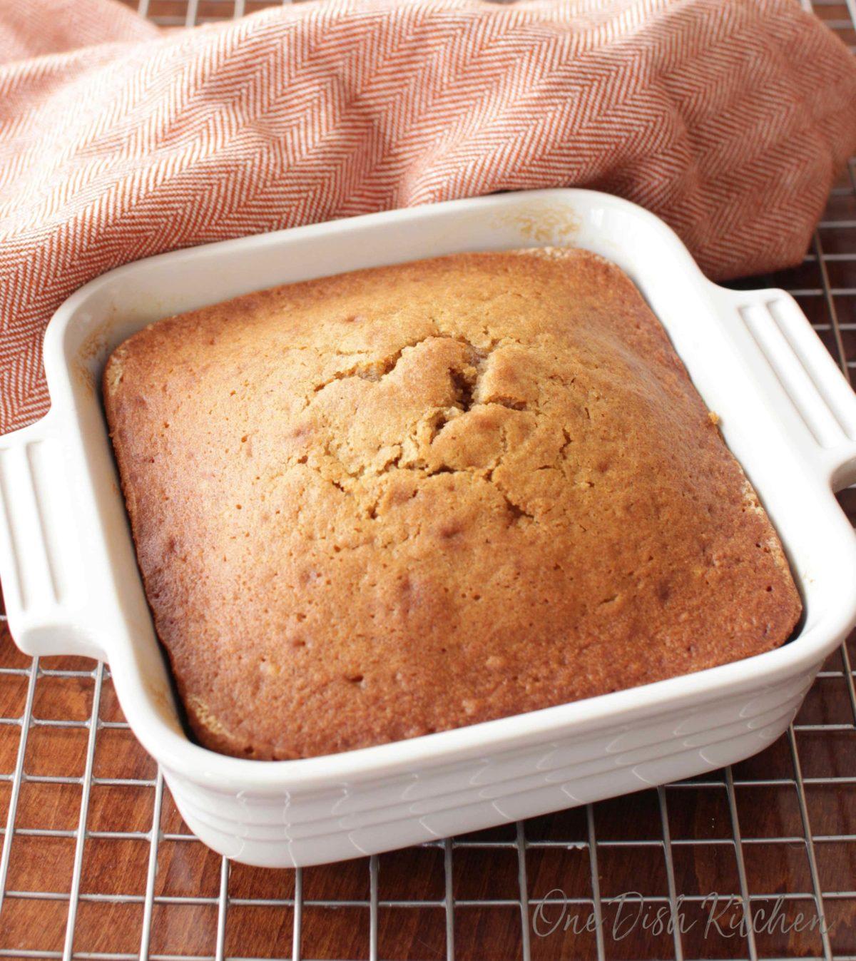 a small square pumpkin cake in a white baking dish.