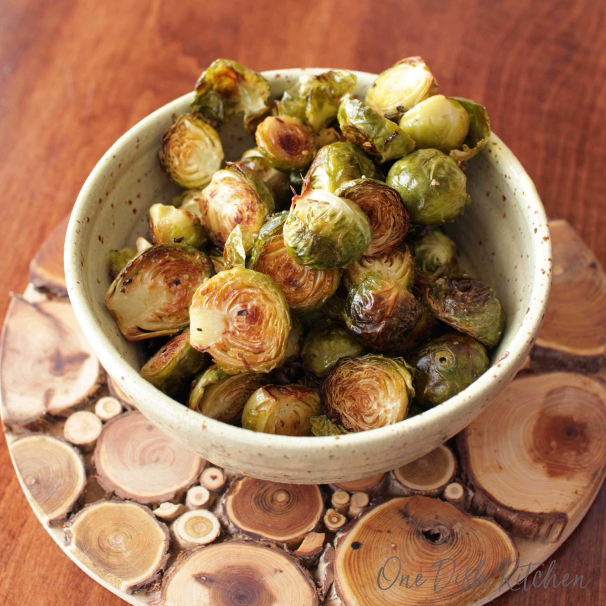 a yellow bowl filled with roasted brussels sprouts.