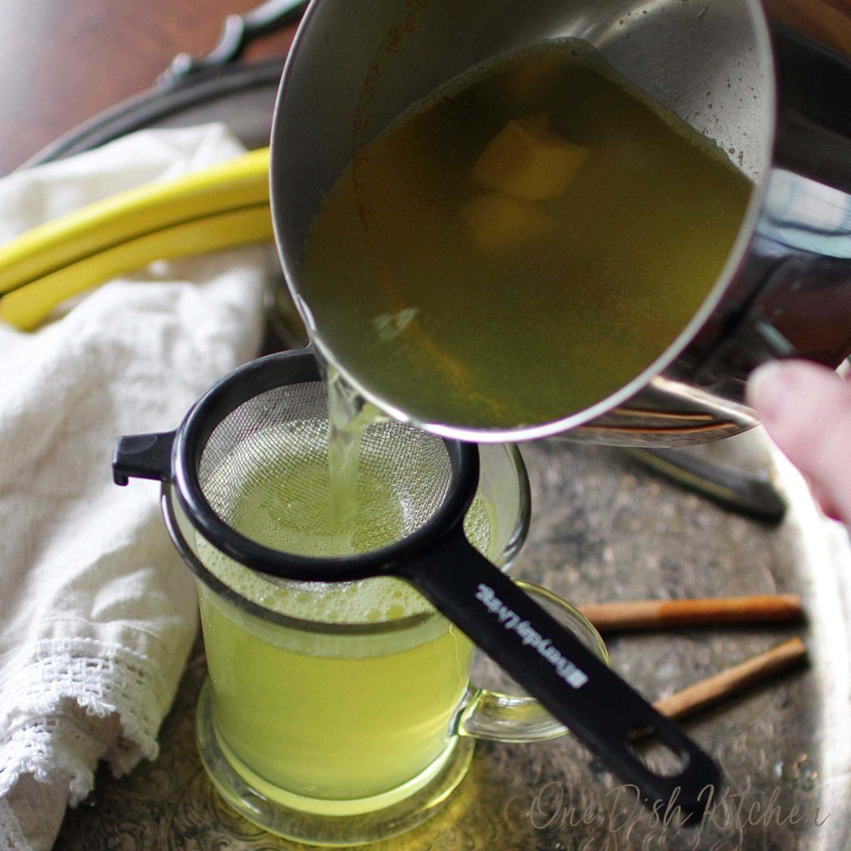 pouring tea through a strainer and into a mug