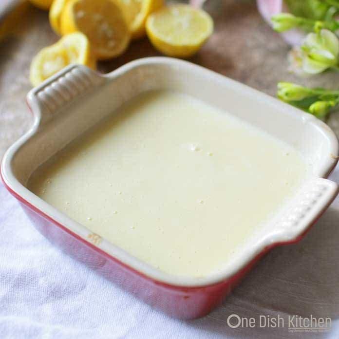 Lemon filling for lemon bars in a small baking dish on a tray with lemon halves