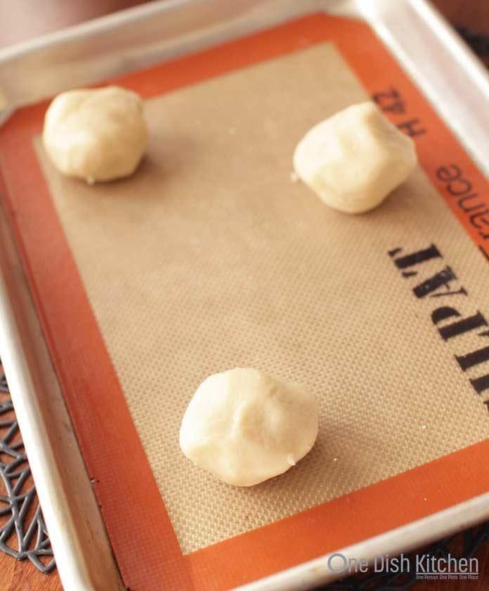 Three shortbread cookie dough balls on a baking sheet