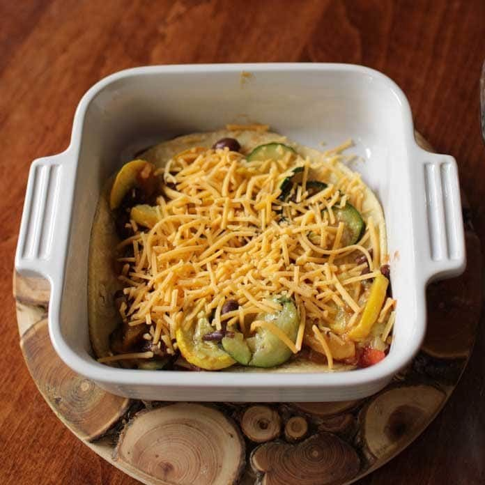 cheese covering sauteed vegetables in baking dish