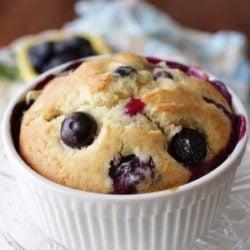 a single blueberry muffin in a small ramekin on a plate.