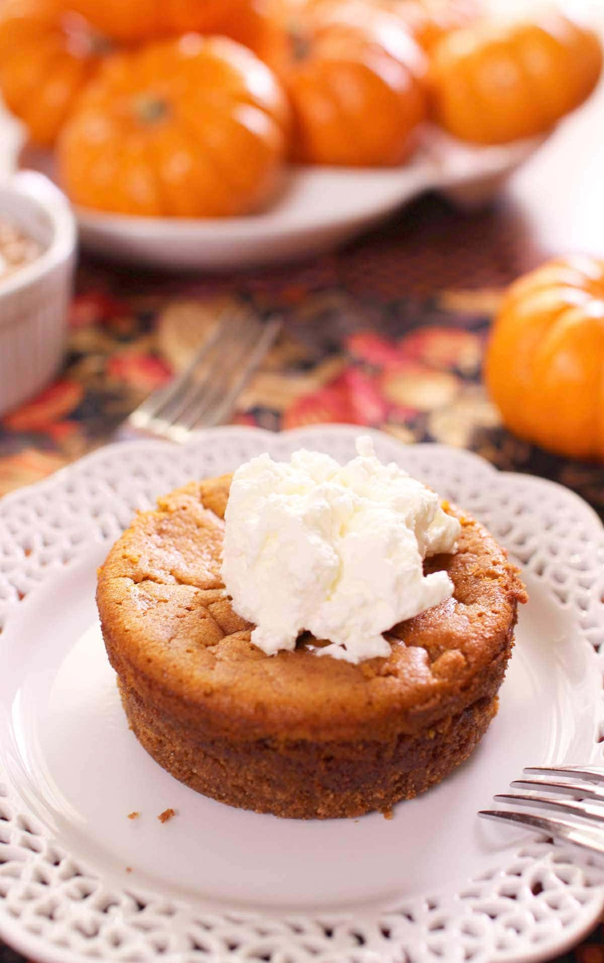A mini pumpkin pie topped with whipped cream on a small plate with  a bunch of small pumpkins in the background