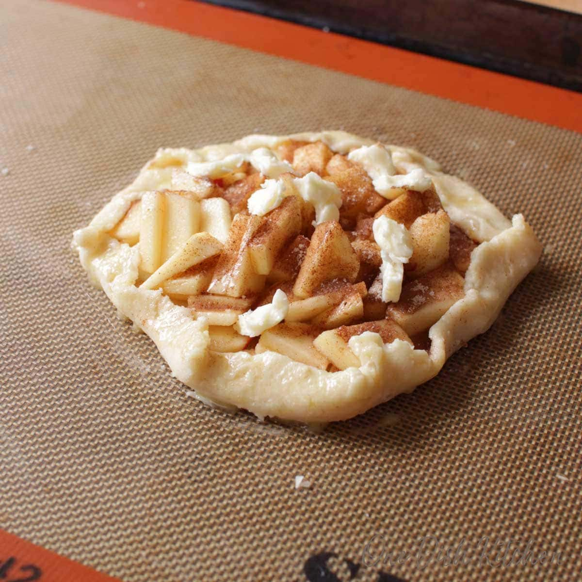 An uncooked mini apple galette on a baking sheet