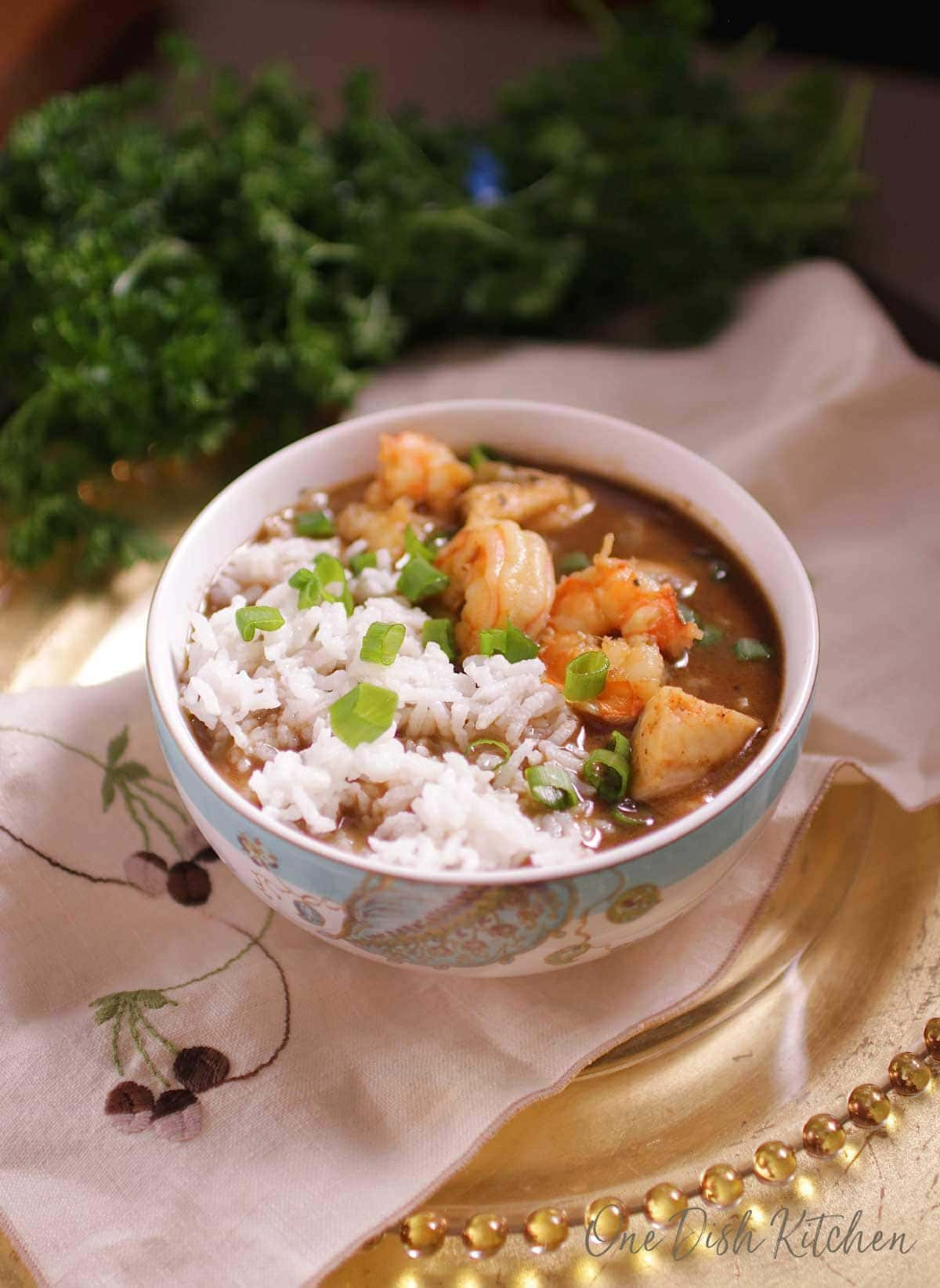bowl of gumbo with shrimp and white rice on a tray with parsley in the background.