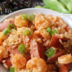 a close up of a white bowl filled with sausage and shrimp jambalaya
