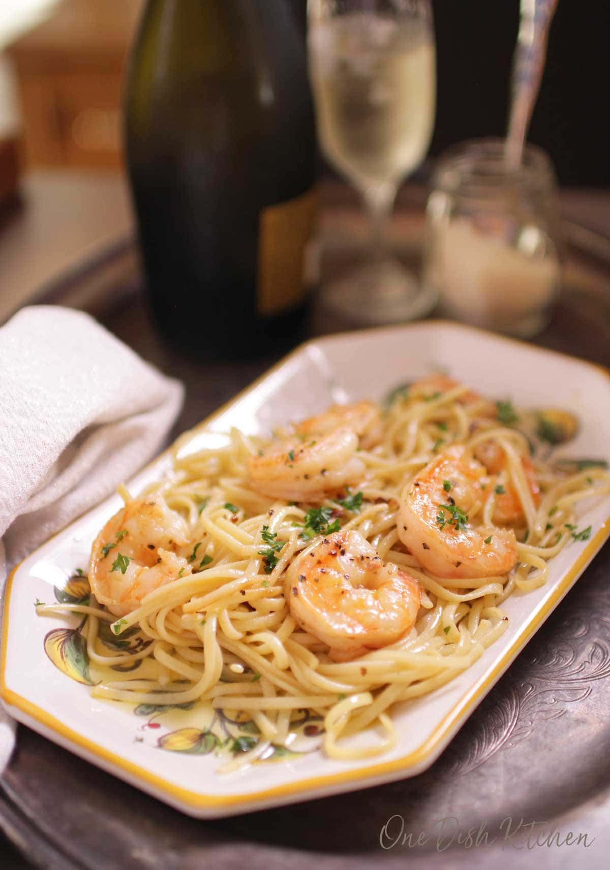 A plate of spaghetti with shrimp on a tray next to a jar of parmesan cheese and a glass of champagne.