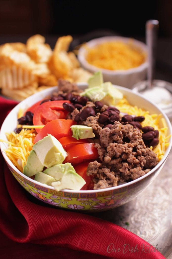 taco salad bowl filled with ground beef, tomatoes, avocados and cheese next to a bowl of chips | one dish kitchen