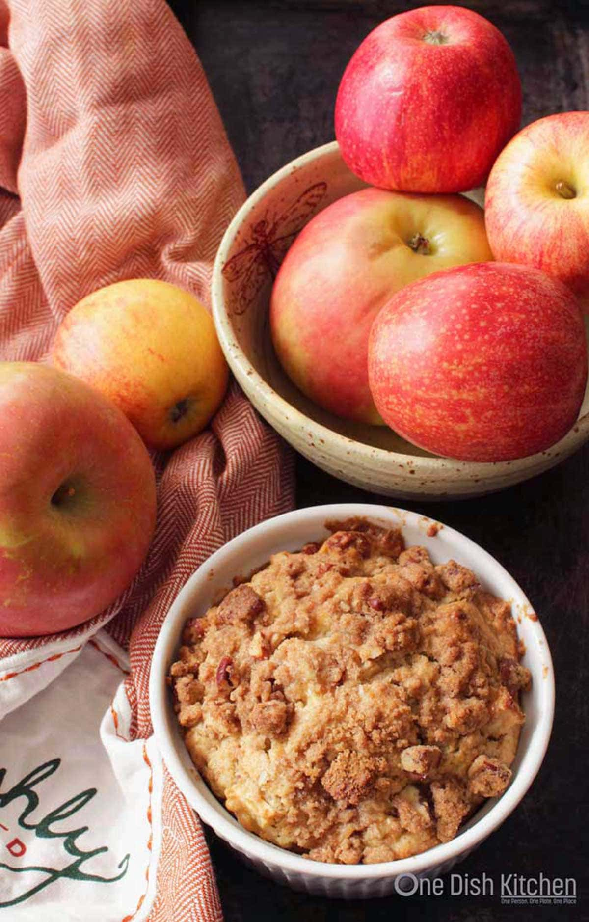 An overhead view of an apple muffin  baked in a ramekin topped with cinnamon streusel next to a bowl of apples