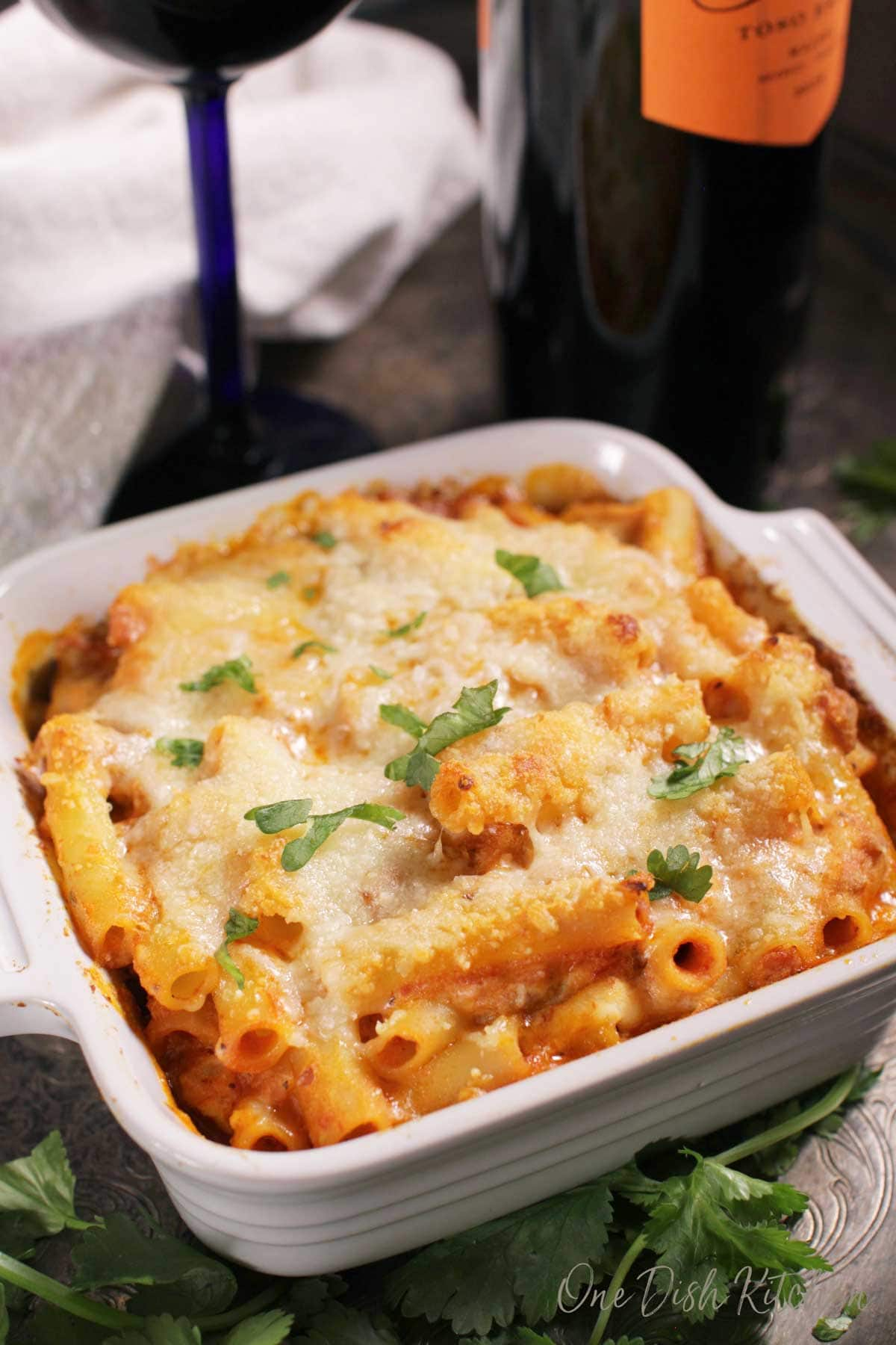 Baked ziti topped with melted mozzarella cheese in a small baking dish garnished with parsley on a metal tray with a glass and a bottle of red wine