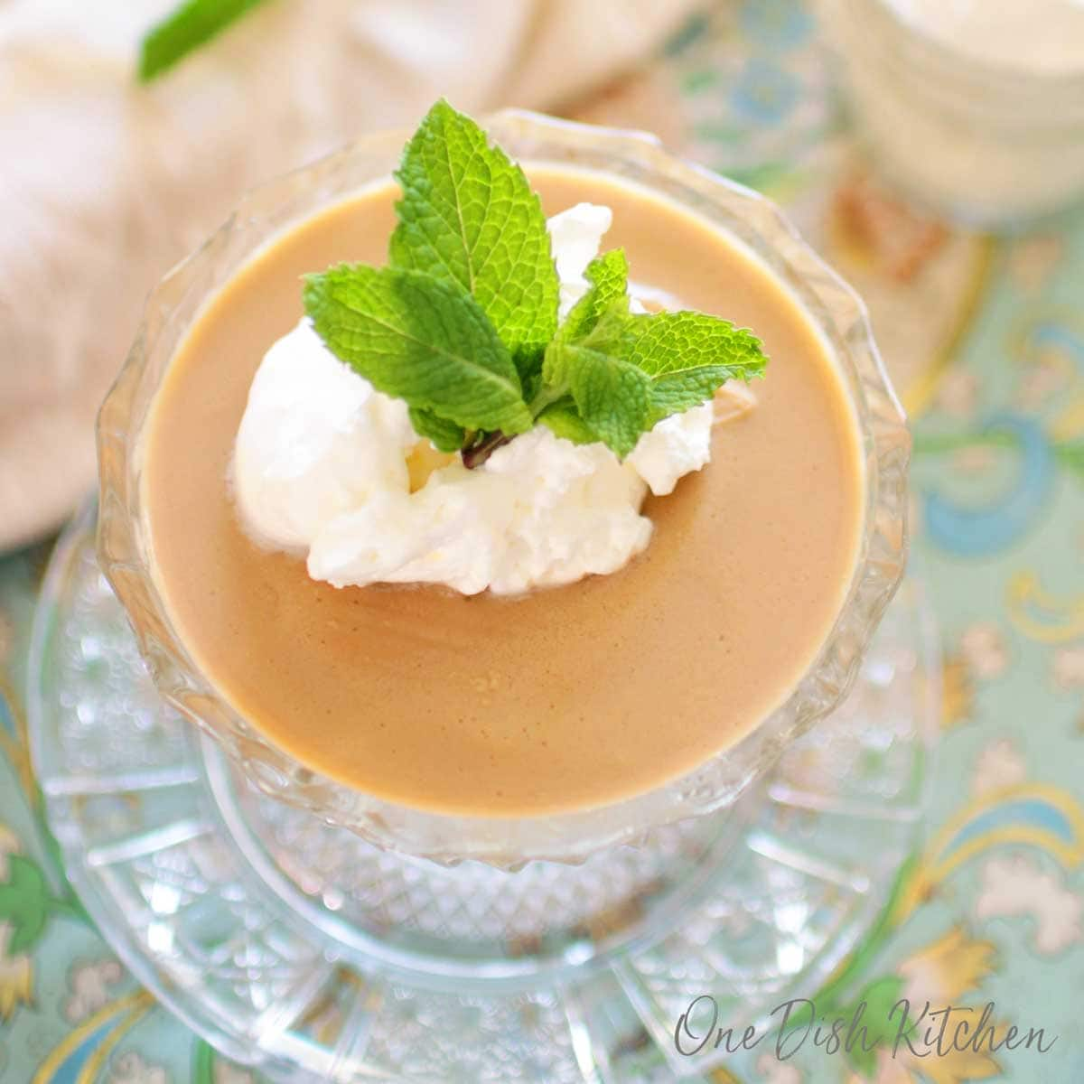 An overhead view of Butterscotch pudding in a dessert glass topped with whipped cream and mint leaves