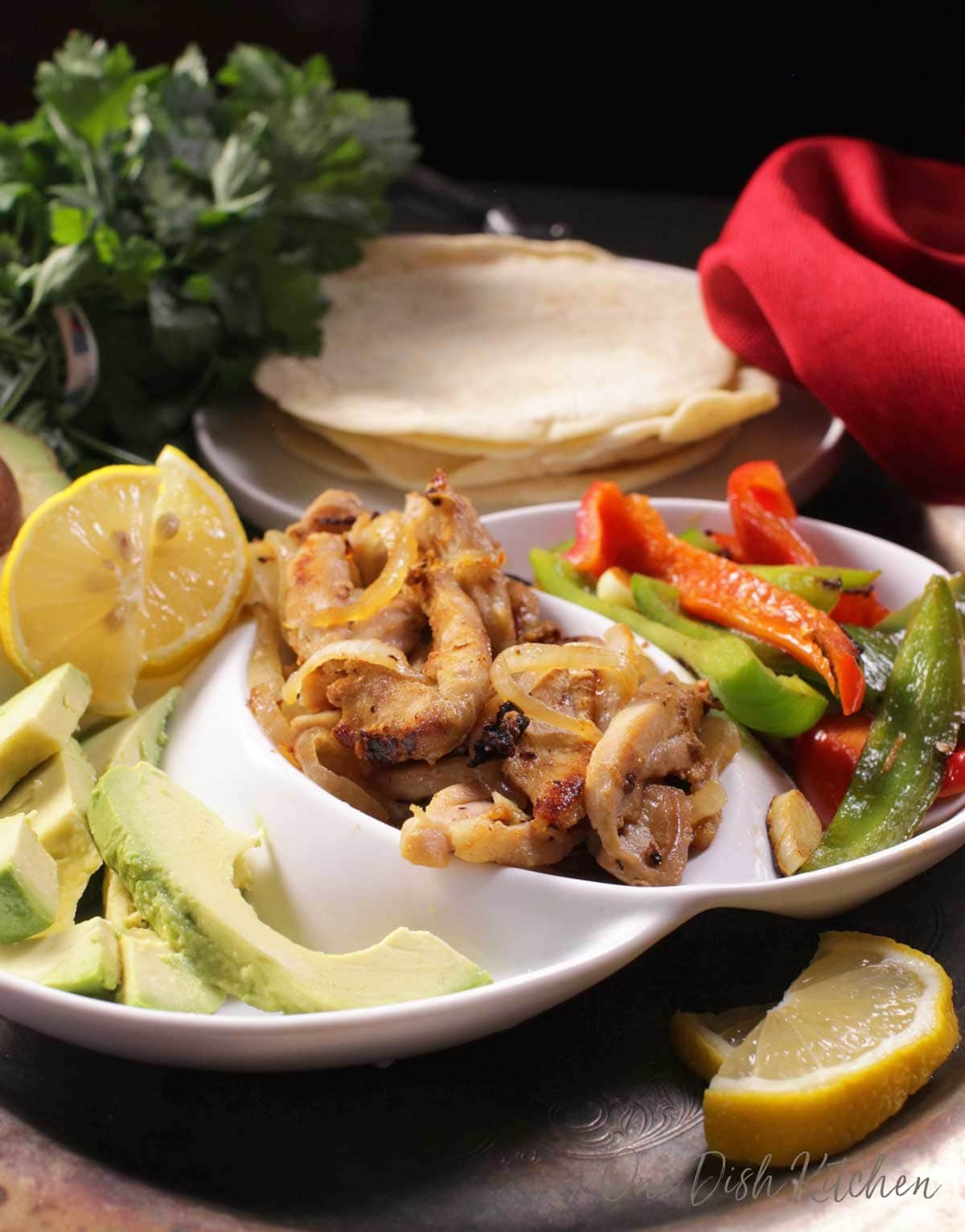A plate of chicken with onions, sliced red and green bell peppers, avocado slices next to a plate of flour tortillas.