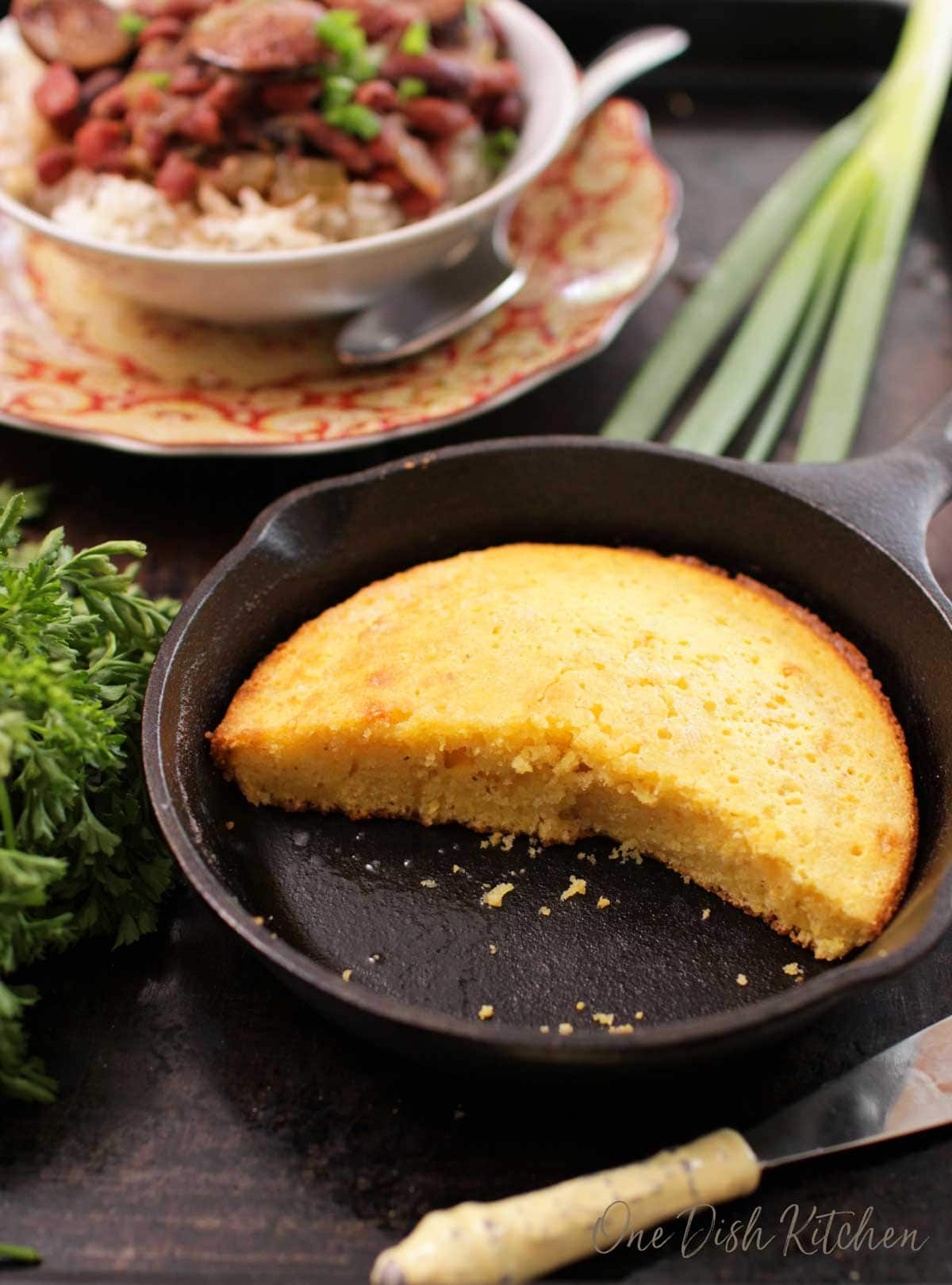 Cornbread cut in half in a small cast iron skillet next to a bowl of red beans and rice