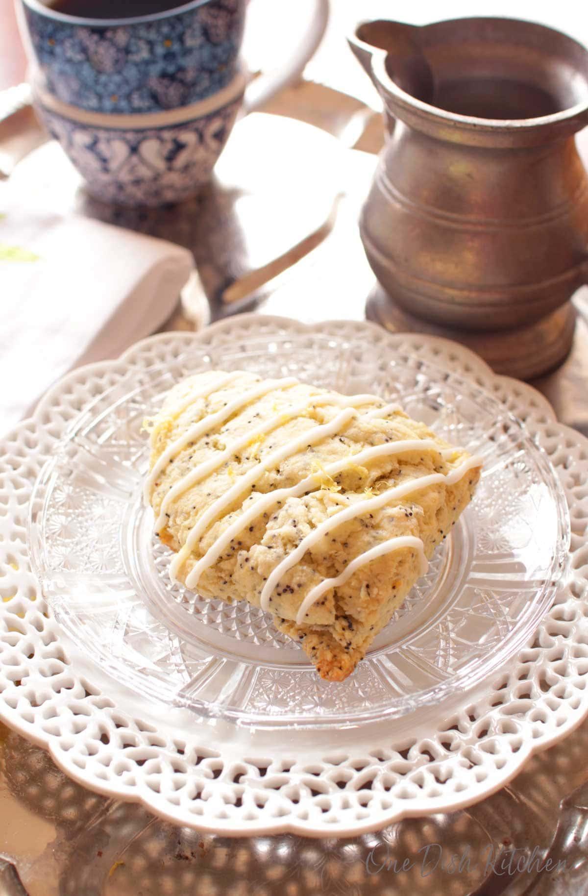 one lemon glazed scone on a plate near a cup of coffee.