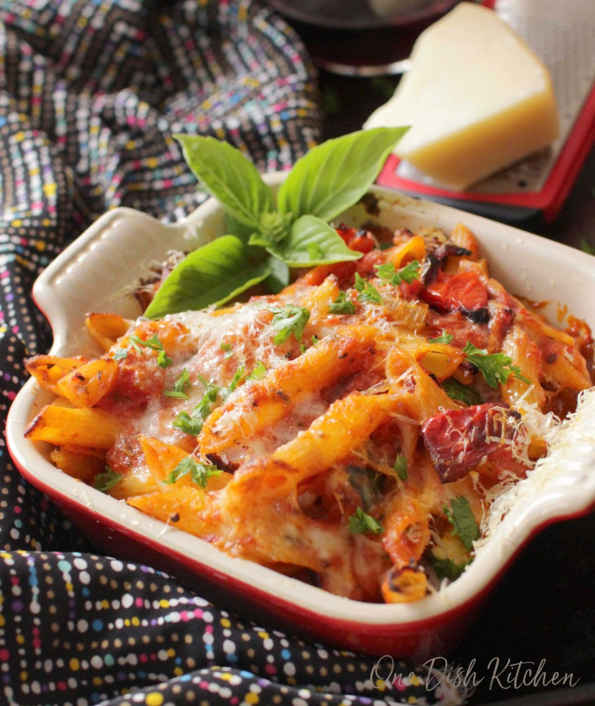 Pasta casserole with bits of roasted red peppers and zucchini arranged in a small baking dish garnished with a sprig of basil on the side and a block of parmesan cheese on a flat cheese grater in the background all on a multicolored cloth