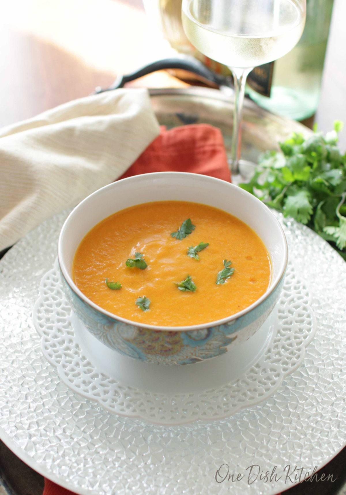 a bowl of carrot soup on a tray next to a glass of white wine.