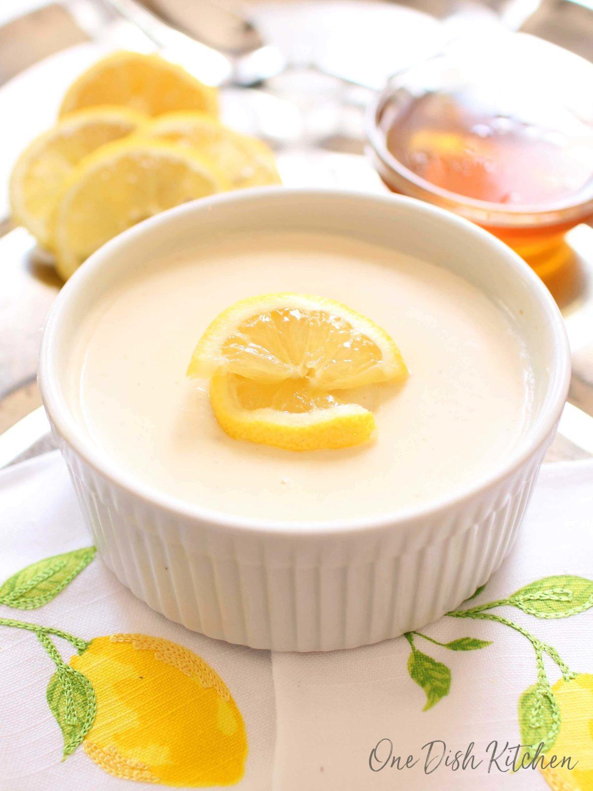 Honey lemon custard in a ramekin next to sliced lemons and a small bowl of honey all on a metal tray