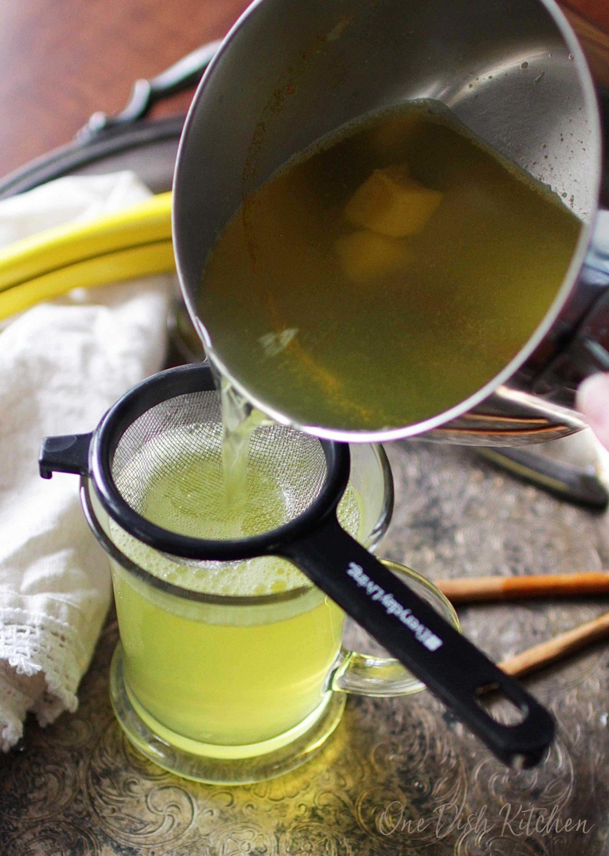 pouring tea into a mug