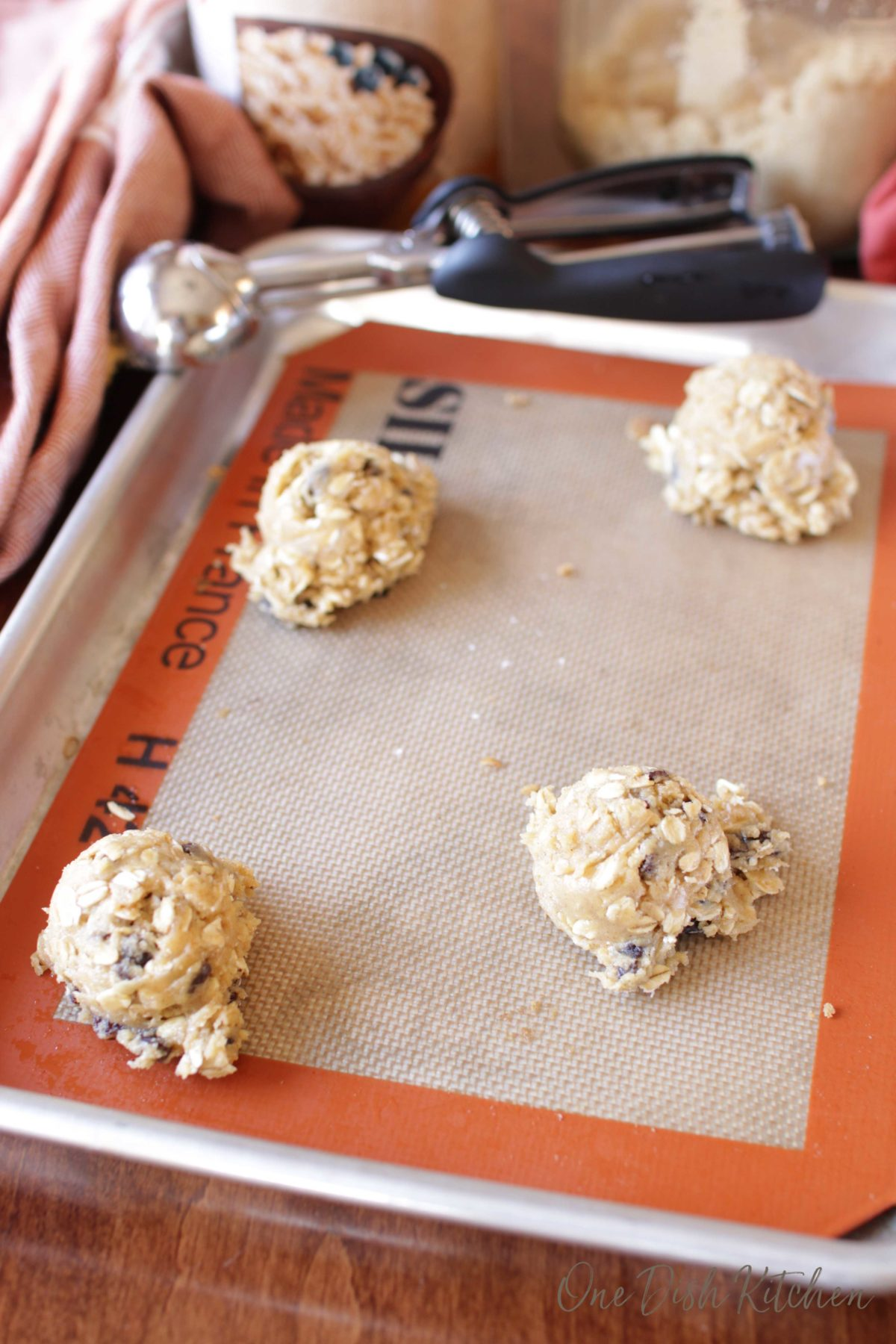 Oatmeal cookie dough on a cookie sheet next to a cookie scoop