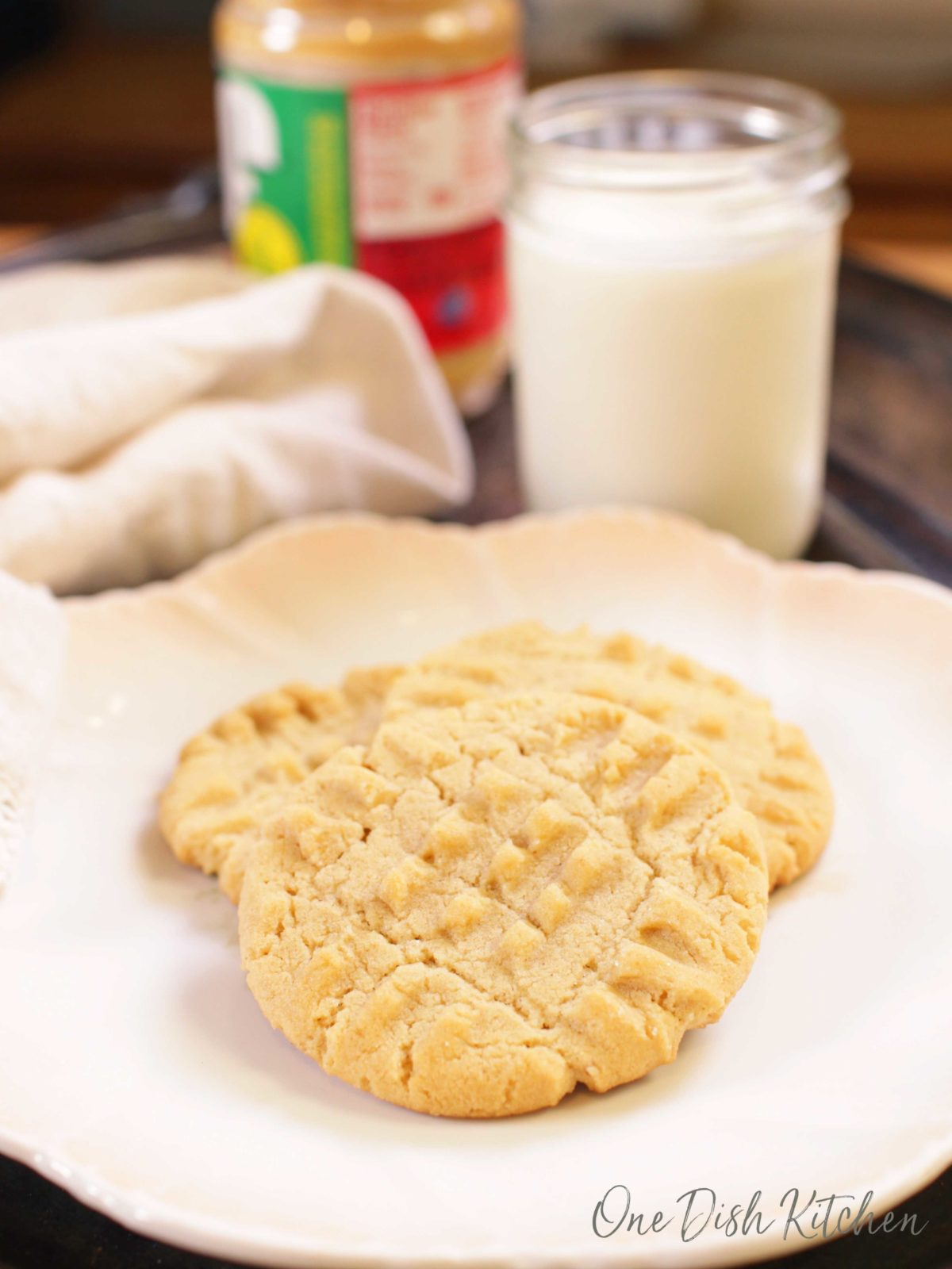 Three peanut butter cookies on a plate next to a jar of peanut butter and a glass of milk.