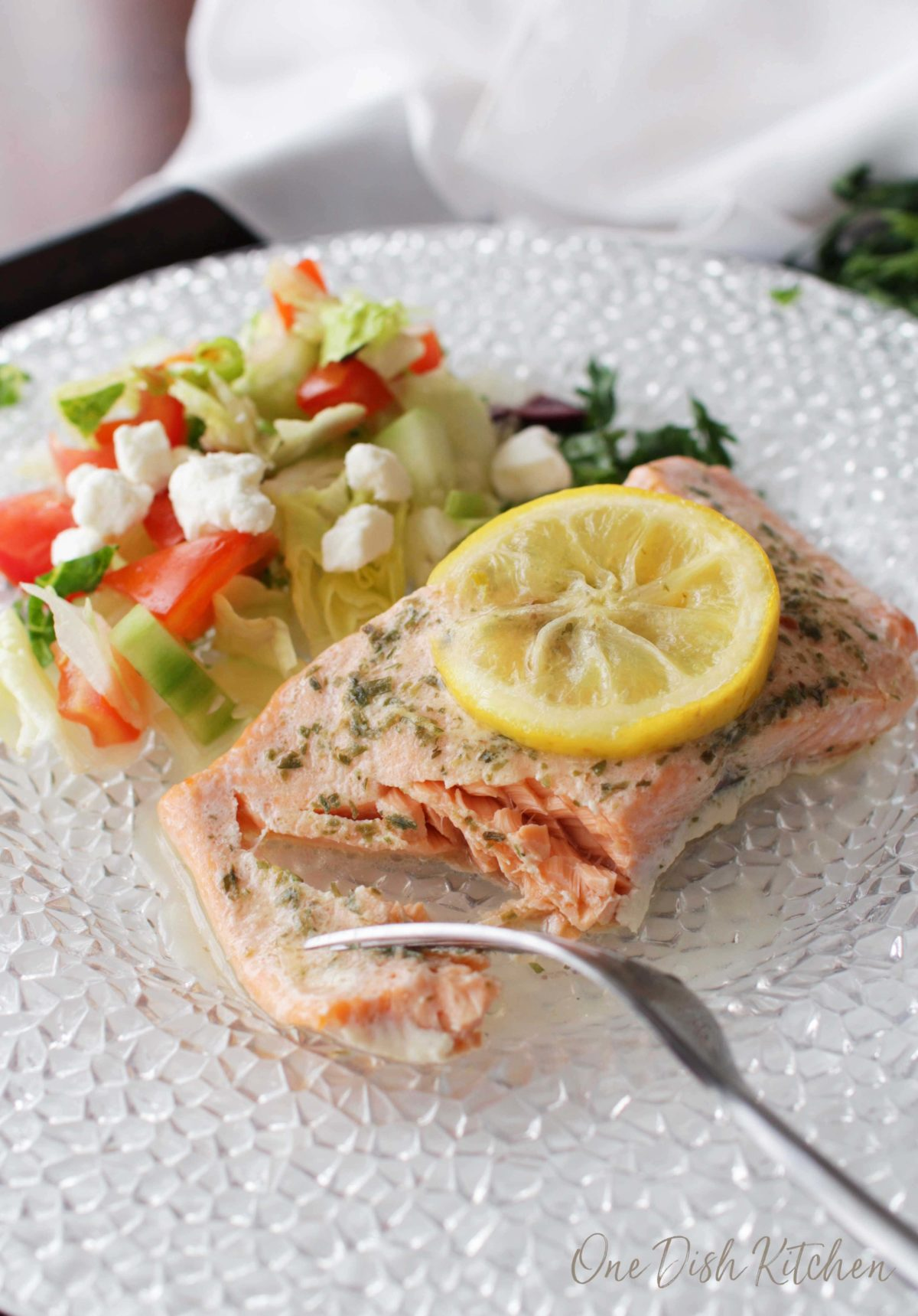 eating a piece of baked salmon with a fork.