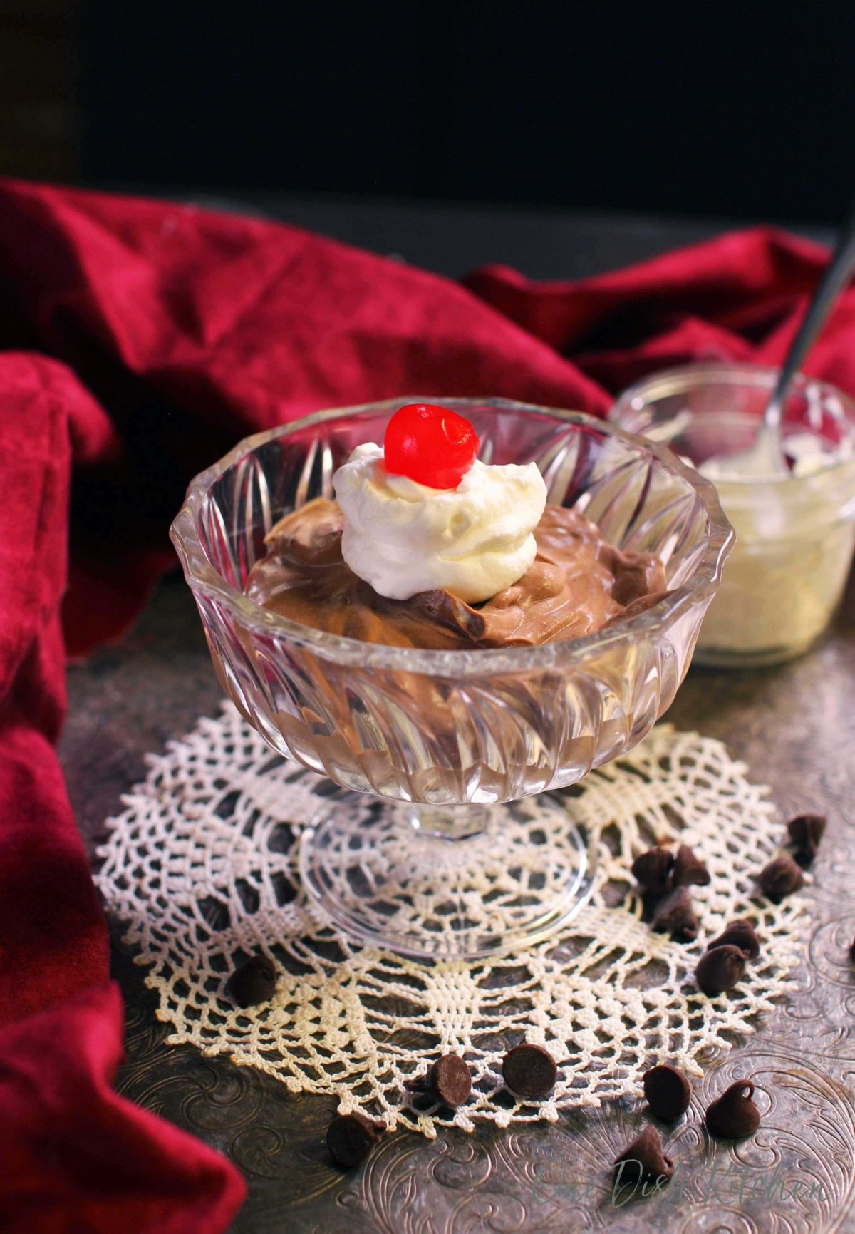 a bowl of chocolate mousse topped with whipped cream and a cherry on a tray next to a red napkin.