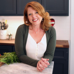 joanie zisk leaning on a counter in the kitchen.
