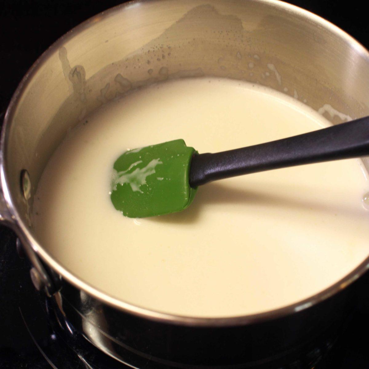 stirring milk in a pot.