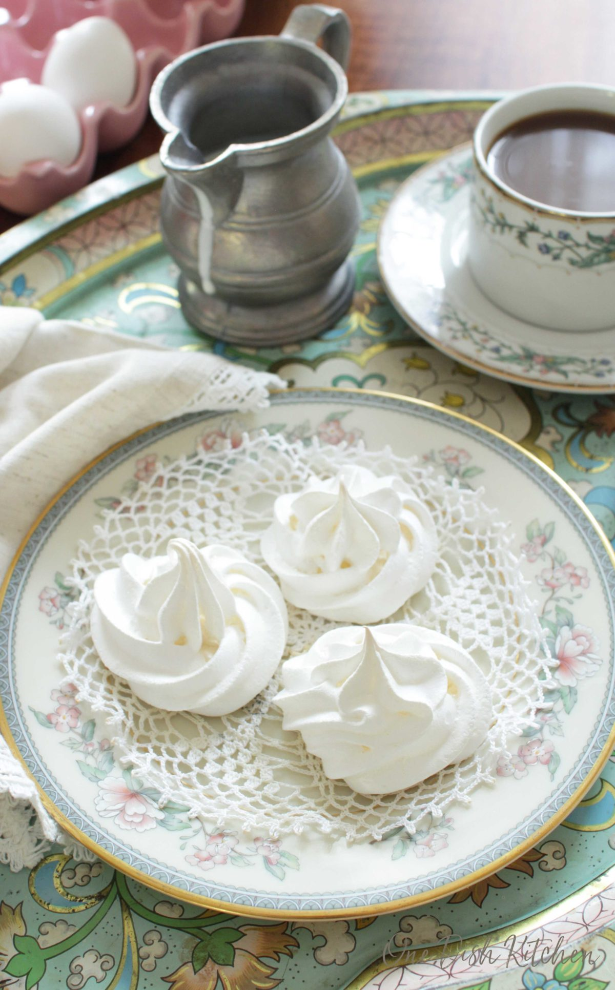 A plate of three meringues on a tray next to a cup of coffee and a small pitcher of cream.