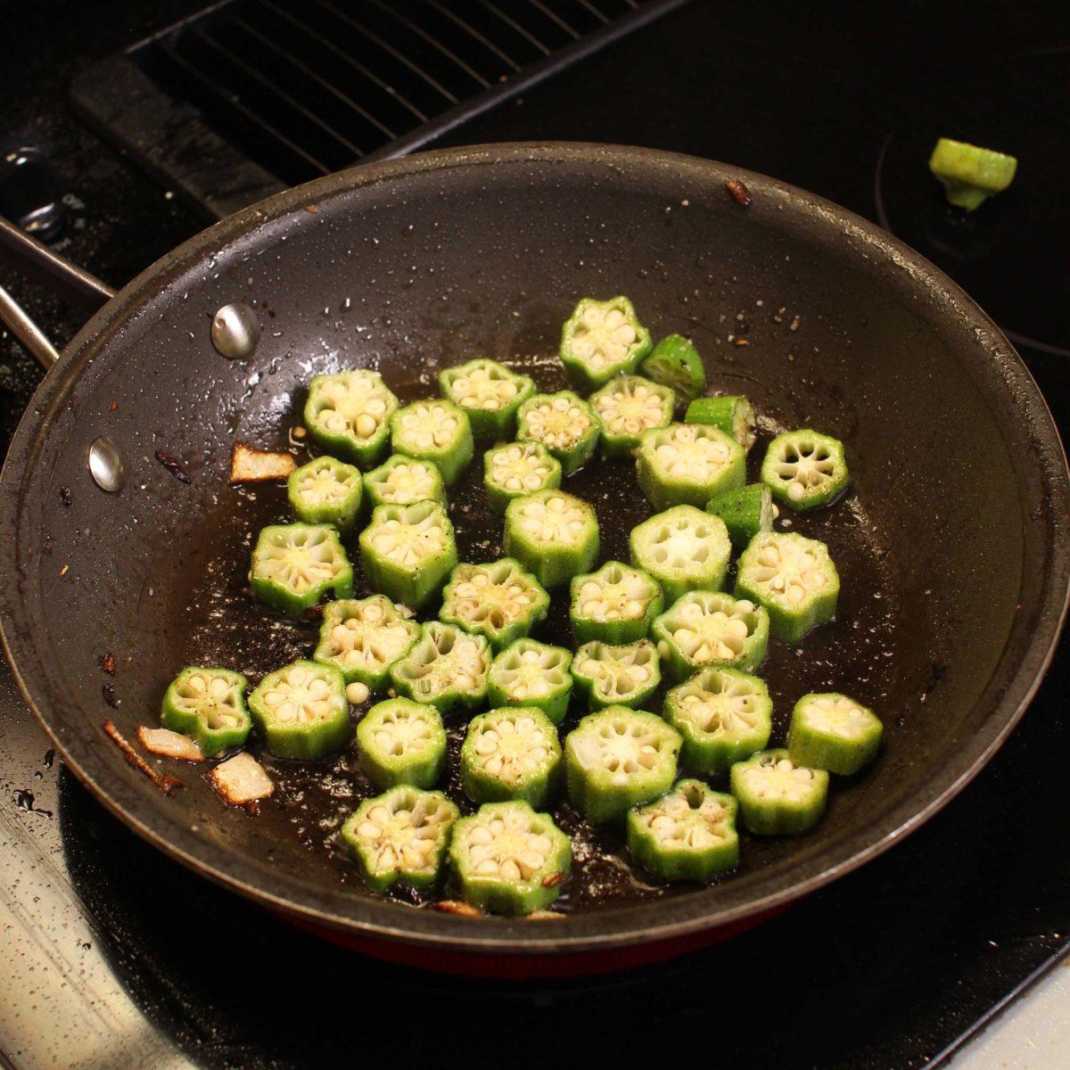 fresh chopped okra in a frying pan.