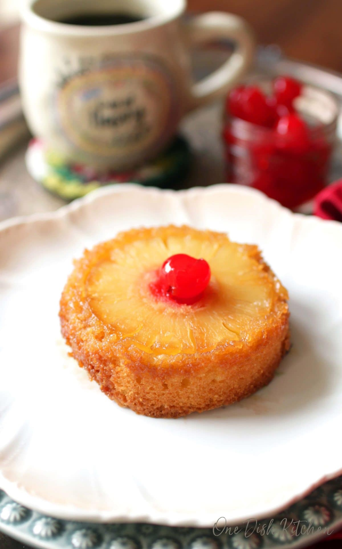 a single pineapple upside down cake on a white plate with a jar of maraschino cherries and a mug of coffee in the background.