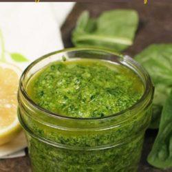 a jar of spinach pesto next to a half of a lemon.