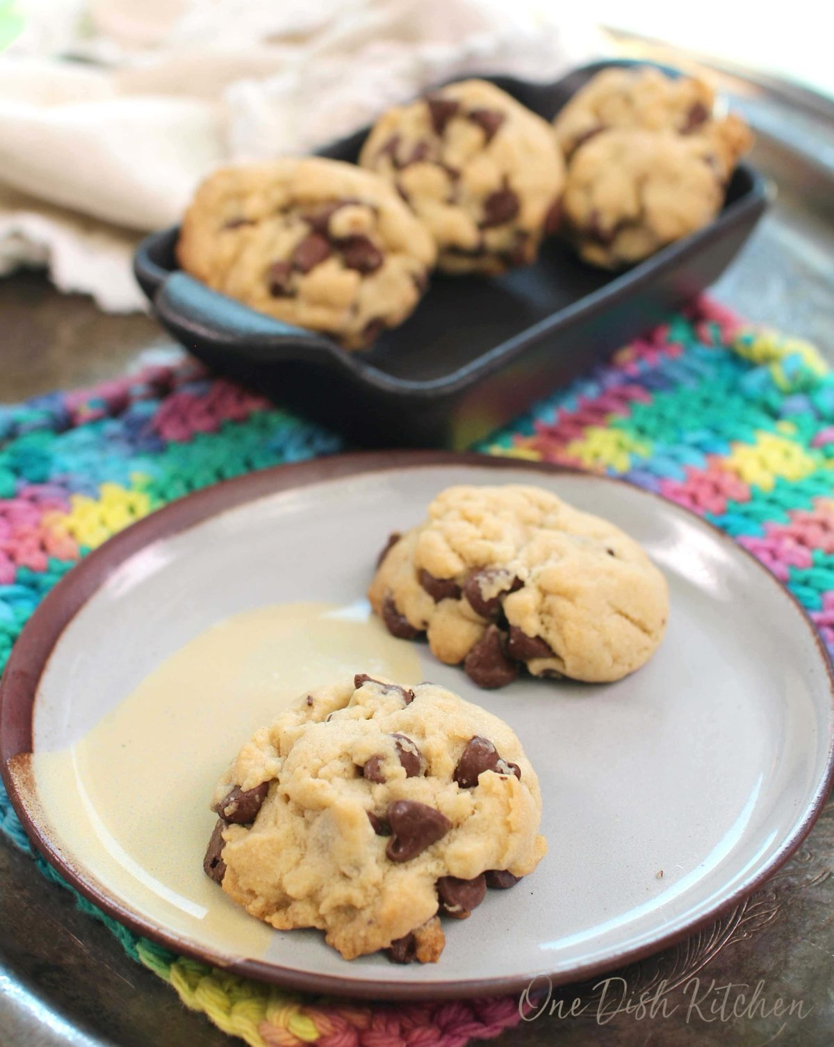 two chocolate chip cookies on a blue plate with a bowl of cookies in the background.