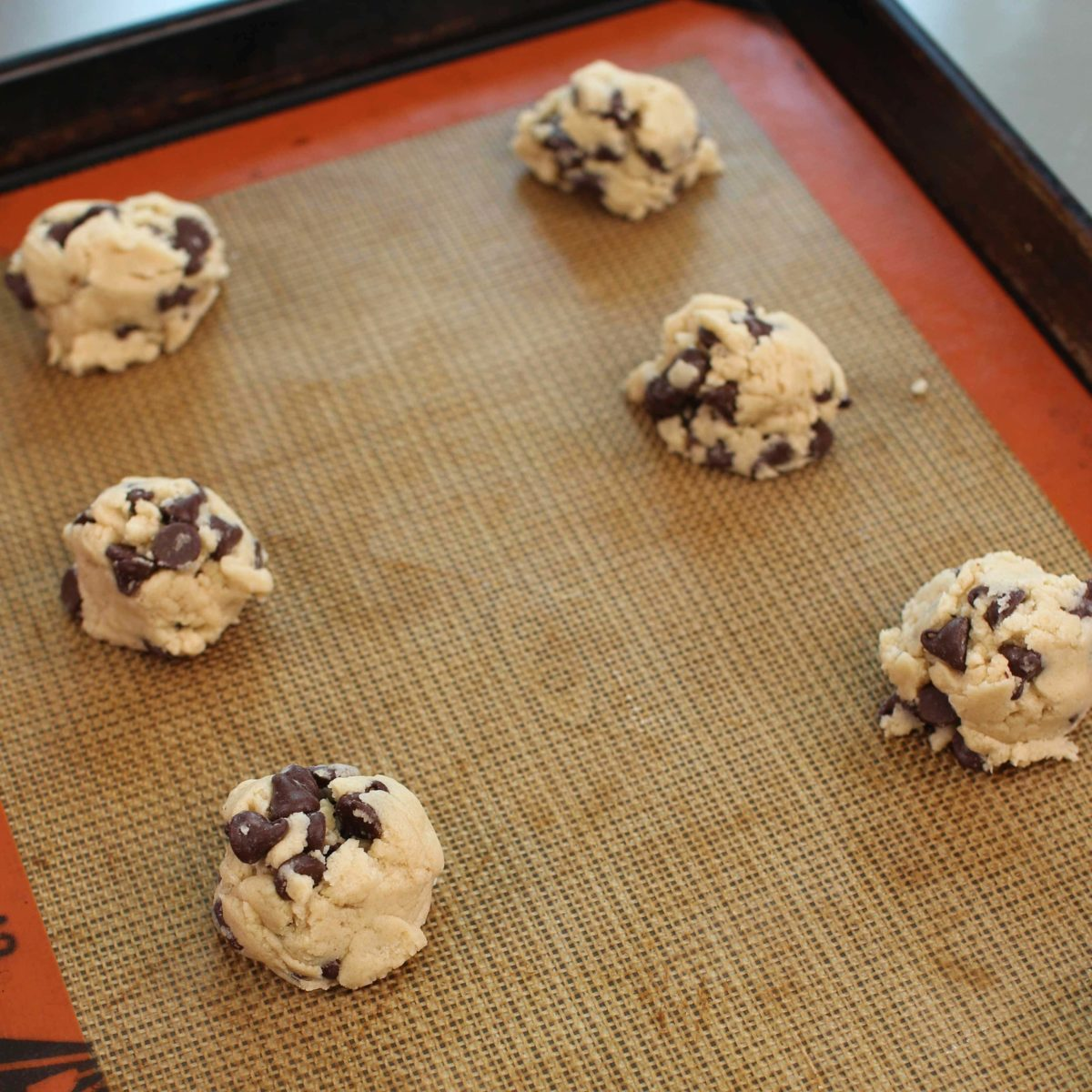 raw chocolate chip cookie dough on a baking sheet